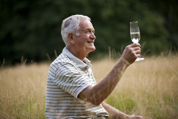 A senior man sitting on the grass, drinking champagne