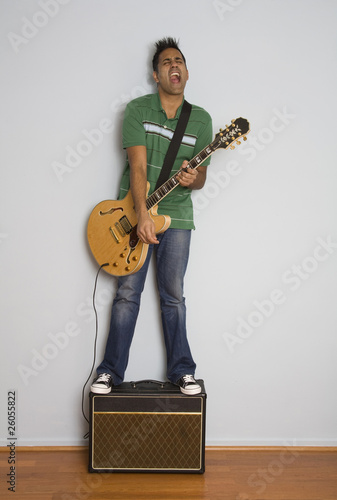 Mixed race man playing electric guitar