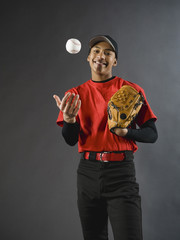 Mixed race baseball player tossing baseball