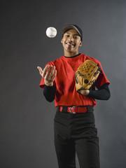 Mixed race baseball player tossing baseball