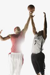 African men jumping for basketball