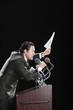 Hispanic man holding document at podium with microphones