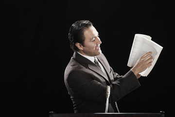 Hispanic man pointing to document text at podium