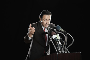 Hispanic man gesturing at podium with microphones