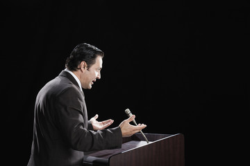 Hispanic man gesturing at podium
