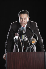 Hispanic man leaning on podium with microphones