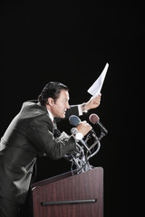 Hispanic man holding document at podium with microphones