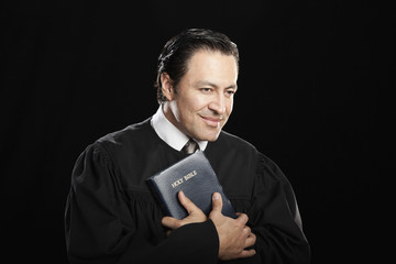 Hispanic pastor holding Bible