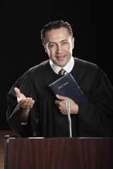 Hispanic pastor holding Bible at podium