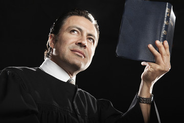 Hispanic pastor holding up Bible