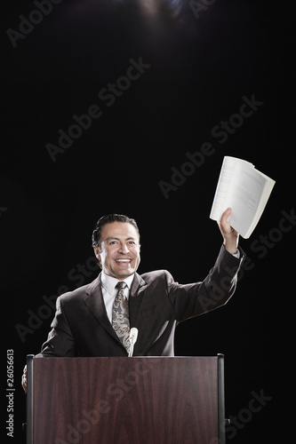 Hispanic man holding document up at podium