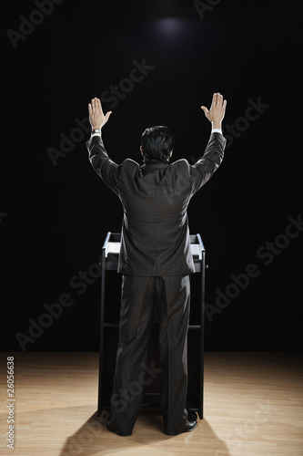 Hispanic man with arms raised at podium