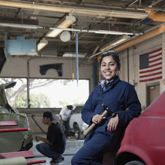 Hispanic worker smiling in auto body shop