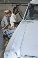 Workers fixing car in auto body shop