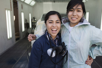 Hispanic workers smiling in auto body shop