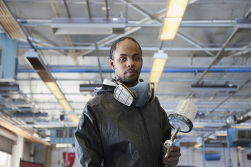 Mixed race man holding equipment in auto body shop