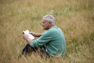 A senior man sitting on the grass, reading a book