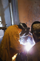 Welders working with grinder