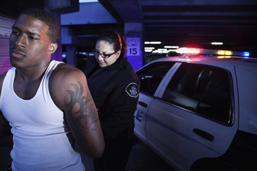 Policewoman handcuffing man