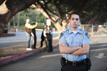 Serious policeman standing with arms crossed