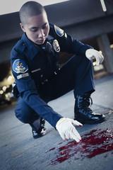 Asian policeman examining blood on ground