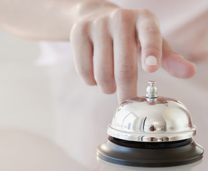 Woman tapping hotel service bell