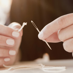 Woman stringing frayed thread through needle