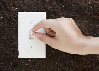 Woman flipping light switch in soil