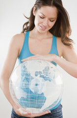 Mixed race woman holding inflatable globe