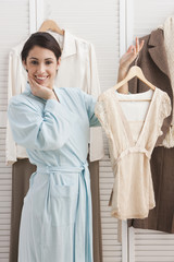 Mixed race woman holding shirt on hanger