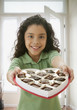 Hispanic girl holding heart-shaped box of chocolates