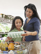 Hispanic mother and daughter shopping at grocery store