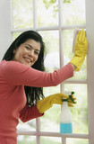 Hispanic woman cleaning window