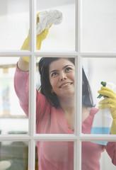 Hispanic woman cleaning window