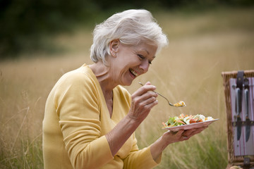 A senior woman sitting on the grass, eating