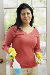 Hispanic woman holding cleaning supplies