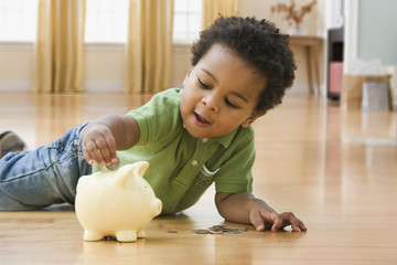 African toddler putting money in piggy bank