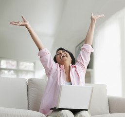 African woman holding laptop with arms raised