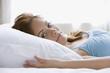 Hispanic woman laying in bed
