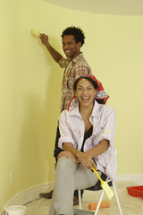 African couple painting walls of room