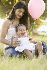 Mother and daughter sitting in field with balloon