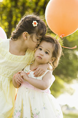 Girl hugging and kissing toddler sister