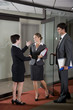 Office workers shaking hands at door of boardroom