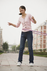 Chinese woman playing with hula hoop