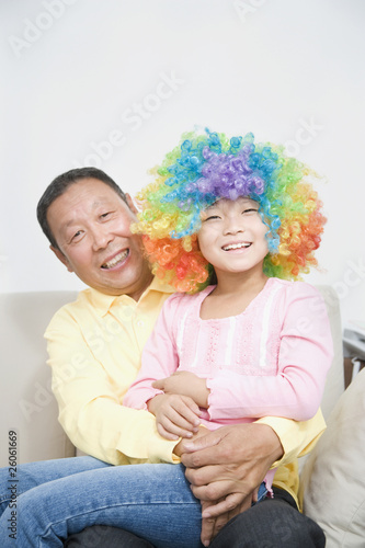 Chinese grandfather holding granddaughter with clown wig