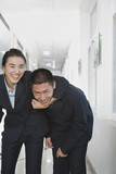 Smiling Chinese businesswoman holding businessman in headlock