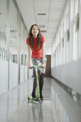Chinese woman riding scooter in corridor
