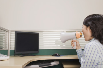 Chinese businesswoman yelling at computer through megaphone