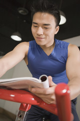 Chinese man reading magazine on exercise bicycle