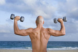 Mixed race man lifting dumbbells on beach